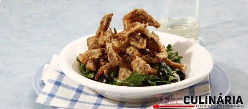 Orelha de porco frita com salada de salsa e azeitonas