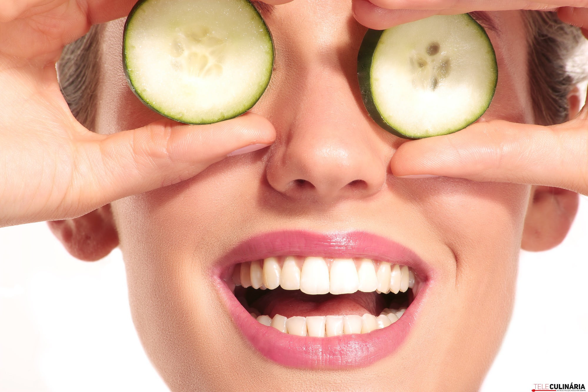 Young beautiflul smiling girl applying a cucumber beauty treatment on white