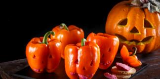 Pimentos laranja recheados com húmus de beterraba decorado para o halloween